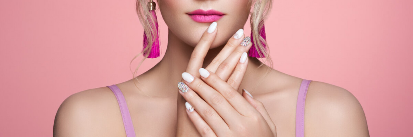 Beauty Woman with perfect Makeup and Manicure. Glamour Girl with Jewelry. Pink Lips and Nails. Precious Stones and Silver. Beauty girls Face isolated on light Background. Fashion photo